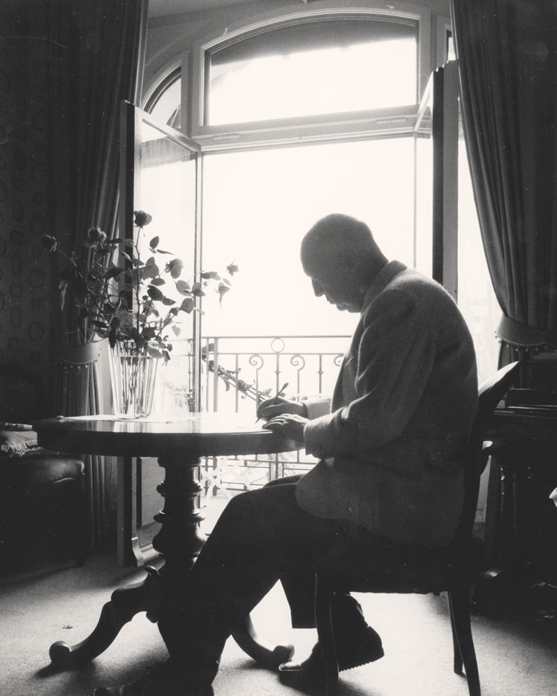 Russian-born author Vladimir Nabokov (1899 - 1977) writes in a notepad while sitting at a table in his suite at the Montreux Palace Hotel, Switzerland.